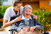 stock photo of geriatric  - Senior woman in nursing home with nurse in garden sitting in wheelchair  - JPG