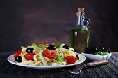 Spaghetti with tomatoes, olives and basil leaves on plate on tablecloth on wall background