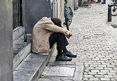 Man Taking A Break On The Sidewalk After Drinking.