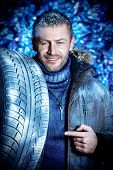 Handsome brutal man dressed in winter clothes covered with frost standing with car tire.