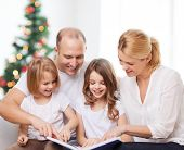 family, childhood, holidays and people - smiling mother, father and little girls reading book over living room and christmas tree background