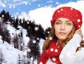 happiness, winter holidays, christmas and people concept - young woman in red hat and scarf over snowy mountains background