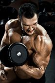 foto of execution  - vertical close up portrait handsome guy bodybuilder execute exercise with dumbbells in dark gym - JPG