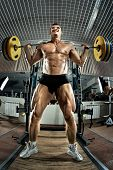 picture of squatting  - very brawny guy bodybuilder execute exercise squatting with weight in gym - JPG
