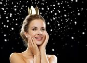 people, holidays, royalty and glamour concept - smiling woman in evening dress wearing golden crown over black snowy background