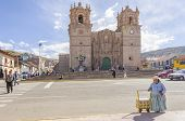 PUNO, PERU, MAY 5, 2014:Plaza de Armas with ice-cream seller and the seventeenth-century Cathedral in the background