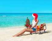 Cute Blonde Woman At Sea Beach In Santa Hat Sitting At Sled With Christmas Tree And Gift Boxes