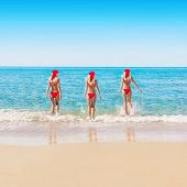 Womans In Christmas Hats On Sea Beach