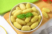 bowl of cooked gnocchi on wooden cutting board