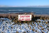 Red Caution Sign On Hazardous Cliff Edge