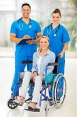 two professional health care workers and disabled patient