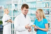 Cheerful pharmacist chemist man giving vitamins to woman in pharmacy drugstore
