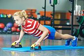 Young woman training pushing up exercises in fitness club gym