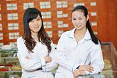 Two cheerful chinese pharmacist chemist woman standing in china pharmacy drugstore