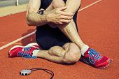 pic of sportive  - Close up of a sportive man who is stretching with stop watch on a stadiums tartan surface after workout - JPG