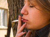 picture of teen smoking  - Young student smoking in front of her school - JPG