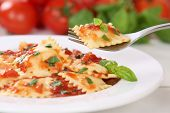 stock photo of pasta  - Eating Italian Pasta Ravioli with tomato sauce noodles meal with basil on a plate - JPG