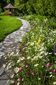 pic of gazebo  - Wildflower garden with paved path leading to gazebo and blooming daisies - JPG