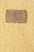 stock photo of millet  - Tag made of burlap lies against the backdrop of millet with place for your creativity - JPG