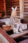 stock photo of bunny ears  - cute happy child girl wearing bunny ears for easter sitting on stairs at country house - JPG