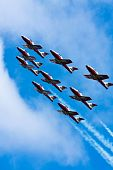 stock photo of snowbird  - Snowbirds full formation climbing synchronously while leaving trails of smoke behind - JPG