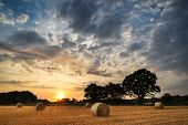 foto of hay bale  - Beautiful Summer sunset over field of hay bales in countryside landscape - JPG