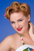 picture of redhead  - Retro styled redheaded woman with fifties hair and makeup blue background - JPG