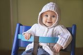 picture of hoodie  - adorable baby girl in a white hoodie sitting in a baby chair and smiling into the camera - JPG