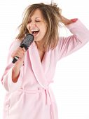 stock photo of housecoat  - Young woman singing with hairbrush - JPG