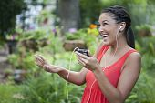 Cute Young Woman Dancing to Music Outdoors