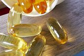 stock photo of prophylactic  - few dietary supplement pills on wooden desk - JPG