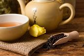 picture of ceremonial clothing  - Horizontal photo of Dry tea leafs in wooden spoon and tea set placed on jute cloth plus yellow tulip bloom all on old worn wooden board - JPG