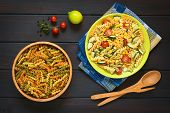 image of pasta  - Overhead shot of raw fusilli pasta in wooden bowl and a plate of vegetarian pasta salad made of tricolor fusilli sweet corn cucumber and cherry tomato photographed on dark wood with natural light - JPG