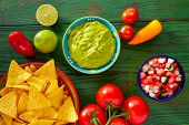 stock photo of nachos  - Mexican food nachos guacamole pico de gallo and chili peppers sauces - JPG