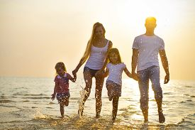 stock photo of sea life  - Happy young family having fun running on beach at sunset - JPG