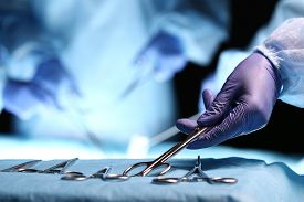 stock photo of surgical instruments  - Nurse hand taking surgical instrument for group of surgeons at background operating patient in surgical theatre - JPG