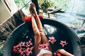 Woman relaxing in round outdoor bath with tropical flowers. Organic skin care in kawa hot bath in lu poster