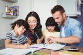 Parents assisting children doing homework at desk poster
