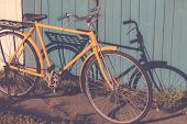 Yellow Old Vintage Bicycle Leaning Against On Vintage Wood Wall Background In The Sun. Bicycle Vinta poster