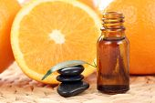 bottle of essential oils and some resh oranges