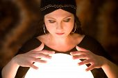 stock photo of witch ball  - Pretty gypsy woman with her hands above her crystal ball predicting the future - JPG