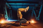 Young cool man break dancer standing on hands upside down. Urban bridge with cool and warm lights ba poster