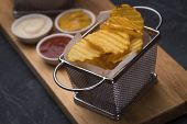 Thick ridge cut potato chips served in frying basket poster