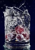 Bunch of red grapes falling down in glass with water on deep blue