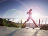 Full Section View Of Fit Slim Man Running On Boardwalk. He Is In Sports Clothing. Determined Sweaty  poster