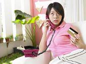 Una mujer joven haciendo algunas consultas sobre su tarjeta de crédito a través de un teléfono