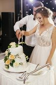 Gorgeous Bride And Stylish Groom Cutting Together White Wedding Cake With Roses At Wedding Reception poster