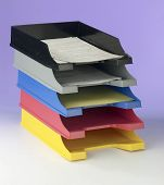Five stackable trays with paperwork.