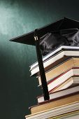picture of graduation cap  - Graduation cap with book  in front of black board - JPG
