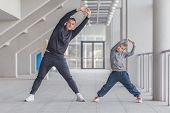 Little Boy And His Father Doing Stretching Legs Exercises  Together At A Sports Center. Father And S poster